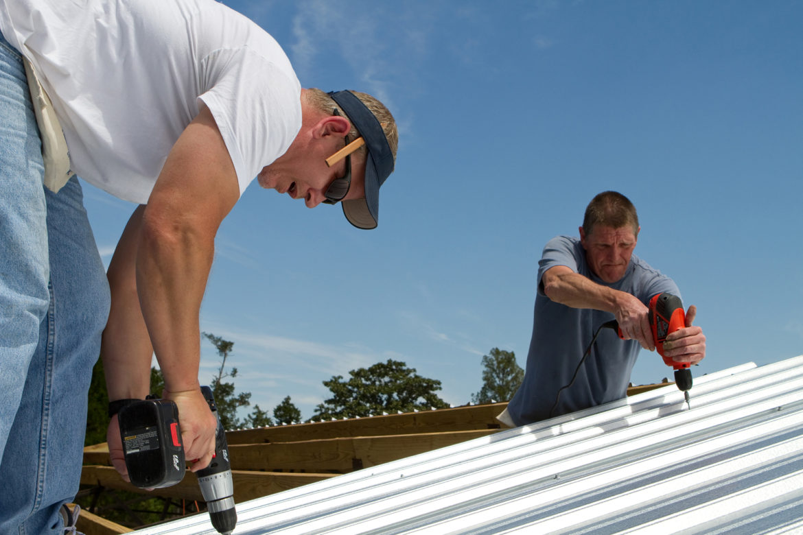 Construction roofing crew uses power tools to screw and fasten sheet metal to the roof rafters of a building.